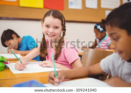 Pupil working at her desk at the elementary school - stock photo