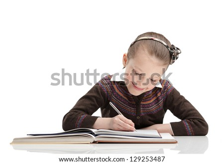 Pupil writes something at her copybook, isolated, white background