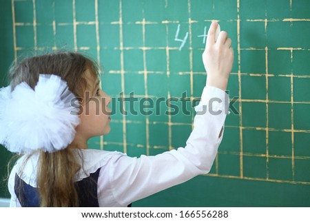 Pupil writing an example on a school chalkboard - stock photo