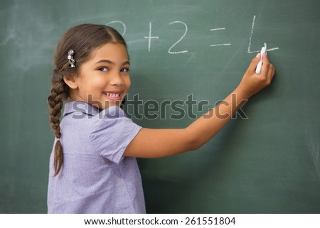 Pupil writing numbers on a blackboard at elementary school - stock photo