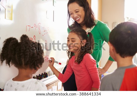 Pupil writing on the board at elementary school maths class - stock photo