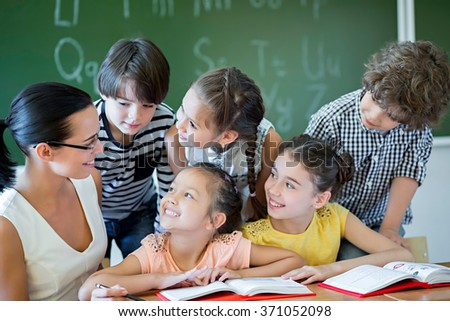 Pupils and teacher in classroom - stock photo