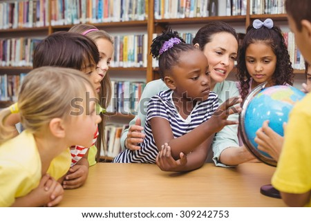 Pupils and teacher looking at globe in library at the elementary school
