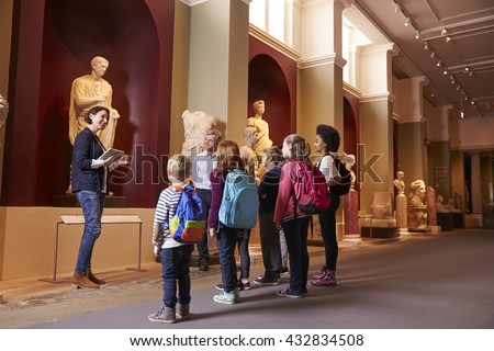 Pupils And Teacher On School Field Trip To Museum With Guide - stock photo