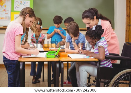 Pupils and teacher working at desk together at the elementary school - stock photo