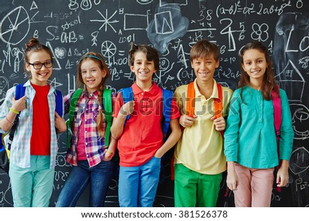 Pupils by blackboard - stock photo