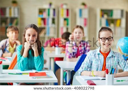 Pupils by desks - stock photo