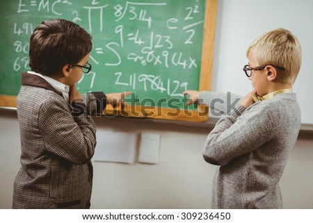 Pupils dressed up as teachers discussing in a classroom in school - stock photo