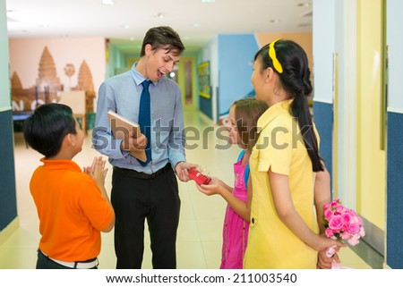 Pupils giving a present to their young teacher - stock photo