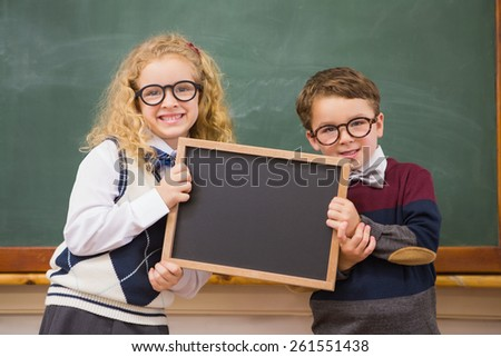 Pupils holding blackboard at elementary school - stock photo