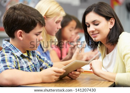 Pupils In Class Using Digital Tablet With Teacher - stock photo