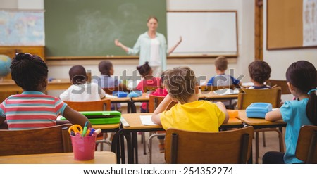 Pupils listening to their teacher at chalkboard in slow motion - stock photo