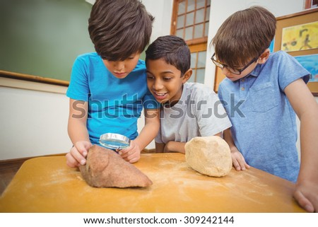 Pupils looking at rock with magnifying glass at the elementary school - stock photo