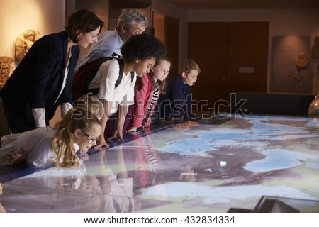 Pupils On School Field Trip To Museum Looking At Map - stock photo