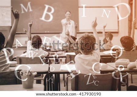 Pupils raising their hands during class at the elementary school - stock photo