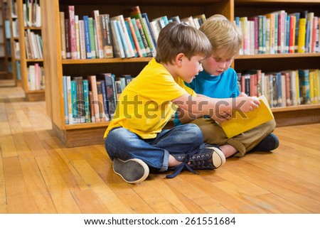 Pupils reading book at elementary school - stock photo