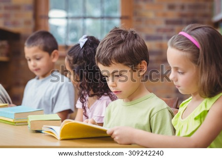 Pupils reading books in library at the elementary school - stock photo
