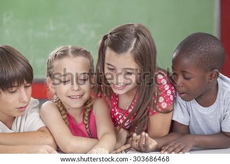 Pupils reading togethers - stock photo