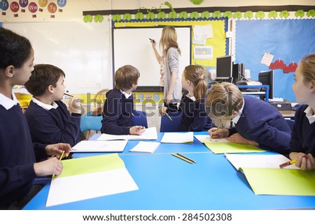Pupils Sitting At Table As Teacher Stands By Whiteboard - stock photo