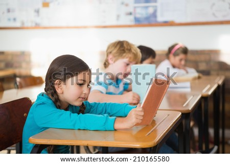 Pupils sitting in classroom reading books at the elementary school - stock photo