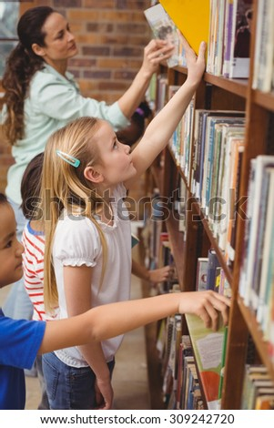 Pupils taking books from shelf in library at the elementary school - stock photo