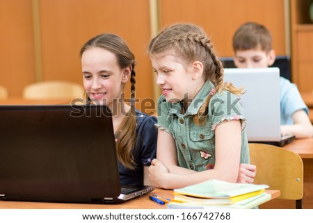 pupils using laptop at lesson - stock photo