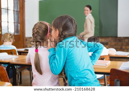 Pupils whispering secrets during class at the elementary school