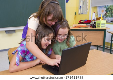 Pupils with computers in school - stock photo