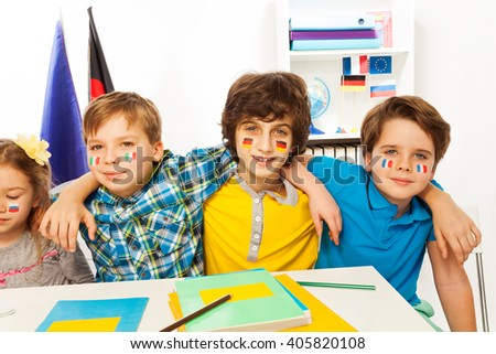 Pupils with flags on cheeks learning languages