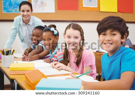 Pupils working at their desks in class at the elementary school - stock photo