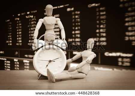 puppet doll and clock with blur perspective stock market number background - stock photo