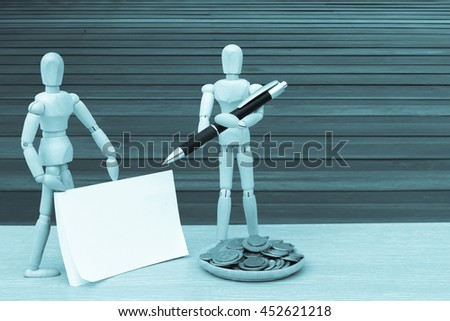 puppet doll ,coins and notepad with wooden floor background