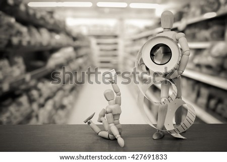 puppet doll holding price tag sticker with blur shop background