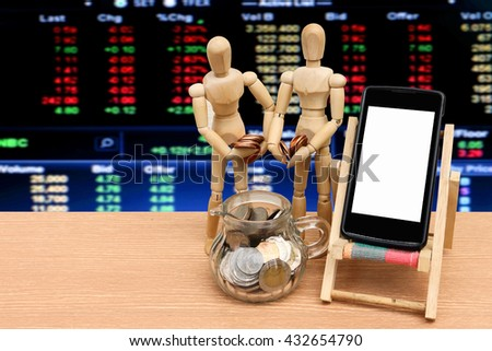 puppet doll put coins to glass jar and mobile phone with blur stock market number background