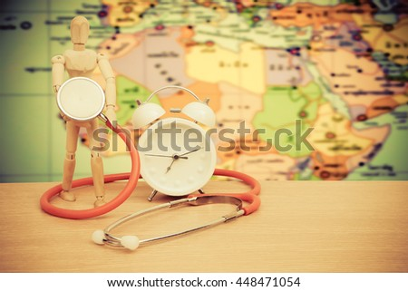 puppet doll ,stethoscope and clock on desk with blur part of world map background - stock photo
