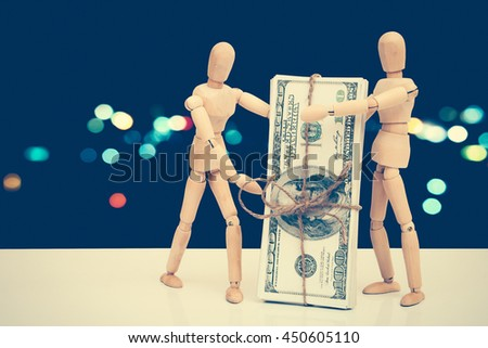 puppet dolls and banknote with  blur bokeh light in city background