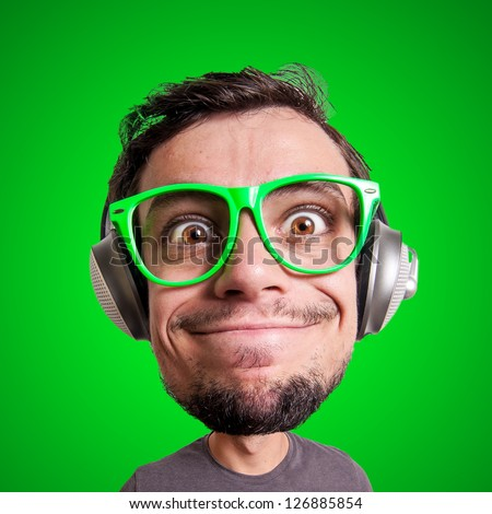 puppet man listening to music with big head on green background - stock photo