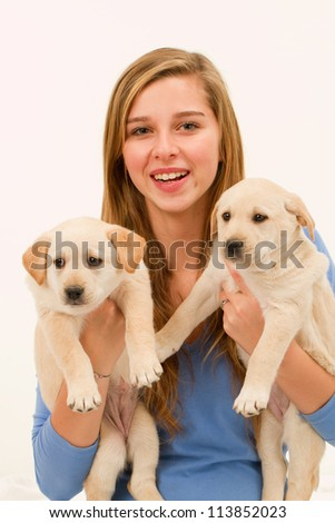 Puppies and happy teenage girl - portrait of young female with her pet dogs