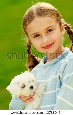 Puppy, child - outdoor portrait of lovely girl with cute puppy, happy childhood concept - stock photo