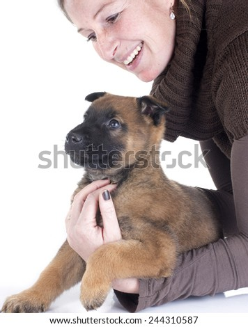 puppy malinois and woman in front of white background
