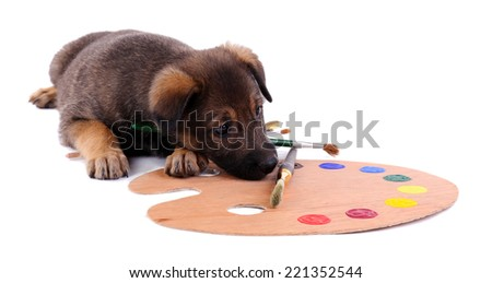 Puppy playing with a palette and brush isolated on white