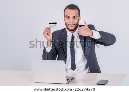 Purchase by credit card. Successful African businessman sitting at a laptop and holding credit card in hand until businessman doing orders through the Internet - stock photo