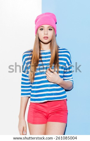 Pure beauty. Beautiful young woman in headwear touching her hair while standing against white and blue background - stock photo