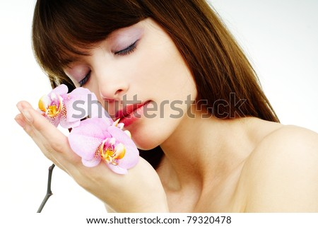 Pure beauty - woman with an orchid - woman with an orchid with her eyes closed - stock photo