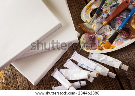 Pure blank canvas and professional acrylics paints in tubes, palette with artistic putty knife and brushes  - stock photo