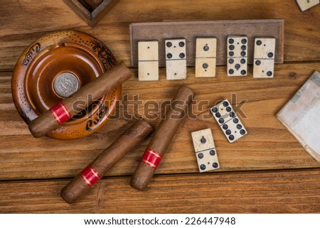 Pure cigars and domino board on table - stock photo