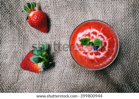 Pure fresh strawberry smoothie glass on hemp cloth, decorated by flower line drawing on topped mixed strawberry yogurt.   - stock photo