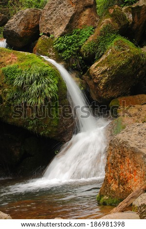Pure fresh water waterfall running over mossy rocks in the forest - stock photo