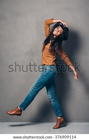 Pure joy and style. Full length of beautiful young African woman in hat posing and looking at camera with smile while standing against grey background - stock photo