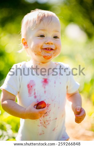 Pure joy - cute happy baby with strawberry, outdoor in garden - stock photo